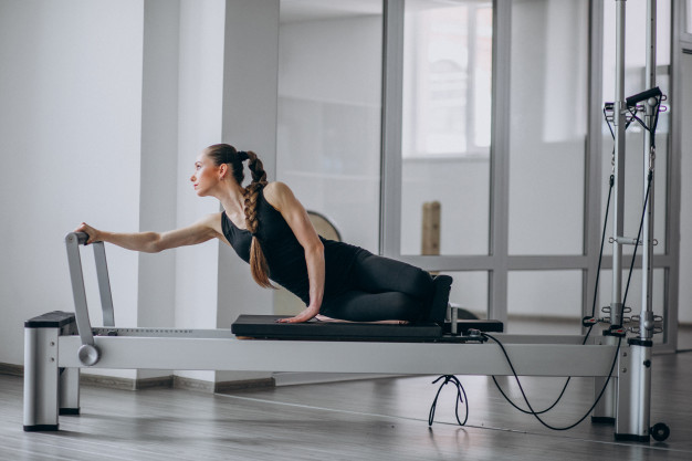 woman-practising-pilates-in-a-pilates-reformer_1303-14778